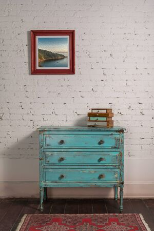 White brick wall with shabby chic vintage turquoise cabinet and hanged painting in living room,