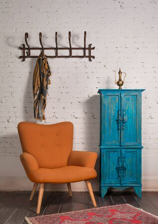 French orange wingback armchair with wooden legs, vintage blue cupboard, and wall hanger with ornate scarf on white bricks wall and grunge wooden parquet with red decorated carpet Stock Photo