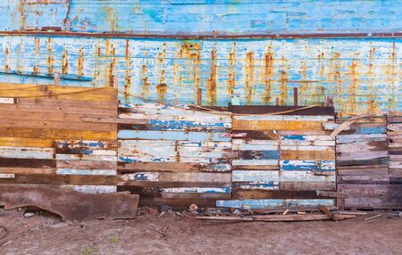 Exterior of paneled aged wooden wall with shabby cracked painting on sandy shore Stock Photo