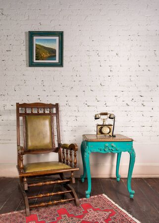 Retro composition of classical leather rocking chair, wooden green vintage table and antique golden telephone set over white bricks wall and wooden grunge parquet floor with red carpet in living room Stock Photo
