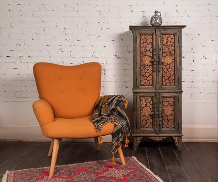 Living room corner with french orange wingback armchair, decorated wooden cupboard, on white bricks wall and grunge wooden parquet with red decorated carpet Stock Photo
