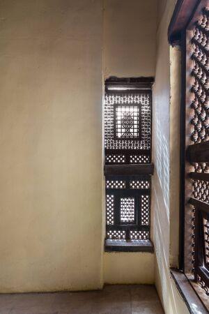 Corner of two Interleaved grunge wooden ornate windows - Mashrabiya - in stone wall in abandoned building