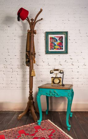 Green wooden vintage side table with golden antique telephone set, and coat hanger stand with red fez and scarf, on room with white bricks wall, hanged painting, and wooden parquet floor