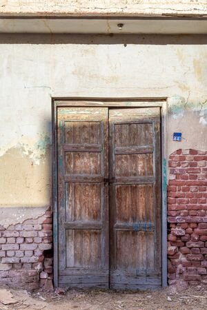 Closed wooden weathered door and shabby old grunge red bricks wall in abandoned district Stock Photo