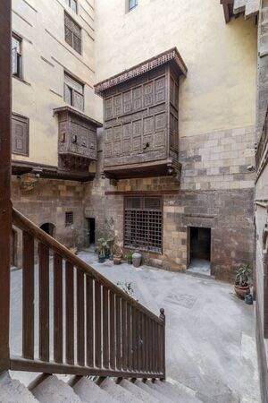 Facade of ottoman era historic house of Zeinab Khatoun with wooden oriel windows - Mashrabiya - and staircase with wooden balustrade located at Azhar district, Medieval Cairo, Egypt