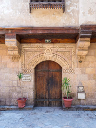 Facade of old stone bricks decorated wall with arched wooden door, Entrance of old Ottoman historic house of Moustafa Gaafar Al Selehdar, Moez Street, Old Cairo, Egypt