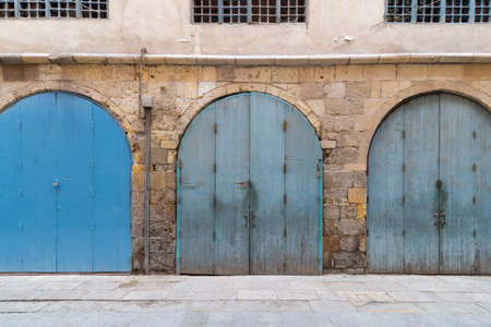 Row of closed three blue weathered wooden arched doors in stone bricks wall, located in old abandoned district