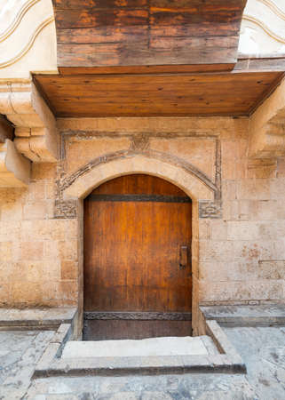 Exterior of aged stone house with weathered walls and arched wooden door, in old town Stock Photo