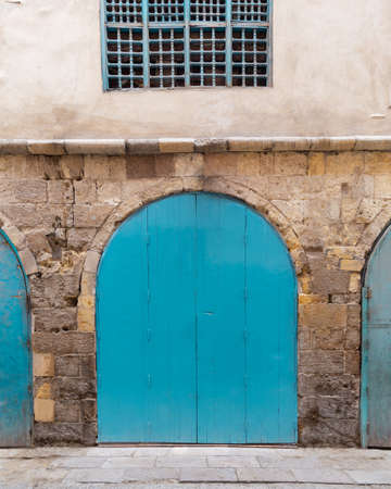 Closed turquoise weathered wooden arched door and wood window grill in stone bricks wall, located in old abandoned district Stock Photo