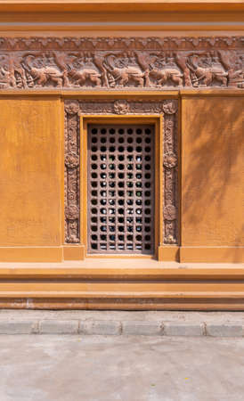 Wooden grid window installed in ornamental wall outside of old stone building Stock Photo