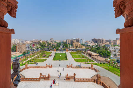 Cairo, Egypt- July 30 2020: View of garden of Baron Empain Palace with Heliopolis district in the far end framed by two decorated pillars at the roof of the palace