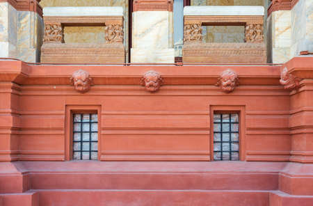 Two adjacent wrought iron grid windows installed in ornamental wall outside of old stone building with decorated balcony balustrade above