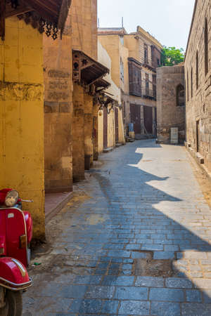 Cairo, Egypt - June 26 2020: Alley branching from historic Moez Street at Gamalia district, old Cairo, during Covid-19 lockdown period with closed shops and no pedestrians