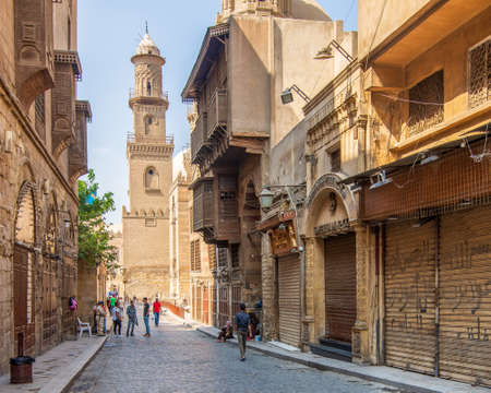 Cairo, Egypt- June 26 2020: Moez Street with workers, few local visitors and minaret of Qalawun Complex historic building, during Covid-19 lockdown period, Gamalia district, Old Cairo
