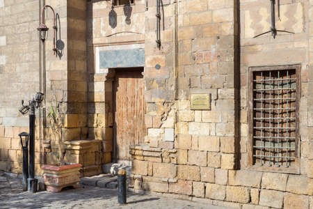 Entrance of historic ottoman era theological school named Madrasa El Ainy with wooden door and decorated wrought iron window over stone bricks wall, located at Azhar district, Medieval Cairo, Egypt