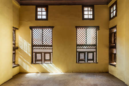 Facade of two Interleaved grunge wooden ornate windows - Mashrabiya - in stone wall in abandoned building Stock Photo