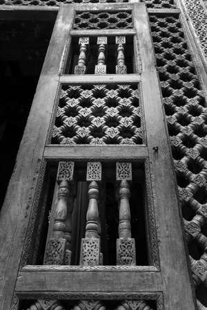 Black and white angle view of wooden carved decorations of interleaved wooden door - Mashrabiya - in abandoned building