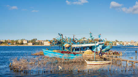 Rashid, Egypt- Feb 1 2020: Fishing boats parked at River Nile in cloudy winter day, El Borg district, Rosetta City, Egypt Editorial