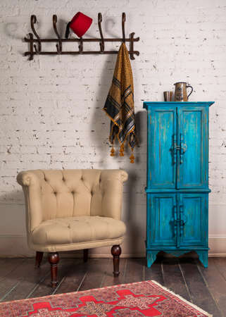 Classic beige armchair with wooden legs, vintage turquoise cupboard, wall hanger, and ornate scarf on white bricks wall and grunge wooden parquet with red decorated carpet Stock Photo