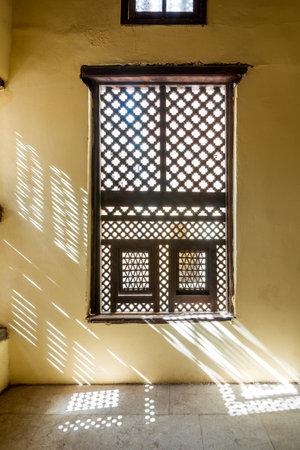 Single interleaved grunge wooden ornate windows - Mashrabiya - in stone wall at abandoned building Stock Photo