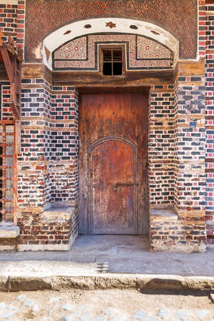 Wooden grunge decorated arched entrance gate with inner small wooden door on wall with black and red bricks with white seam Stock Photo