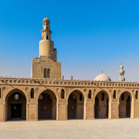 View from courtyard of Ibn Tulun Mosque with its unique design helical outer staircase minaret, and dome and minaret of Amir Sarghatmish mosque in the far end, Sayyida Zaynab, Medieval Cairo, Egypt Stock Photo