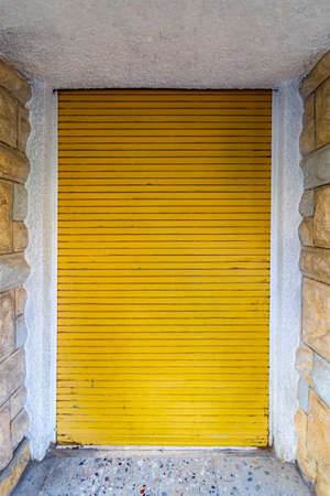 Background of bricks stone wall and closed yellow rolling shutter door Stock Photo