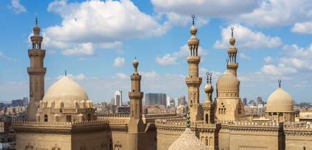 Aerial day shot of minarets and domes of Sultan Hasan mosque and Al Rifai Mosque in cloudy day, Old Cairo, Egypt