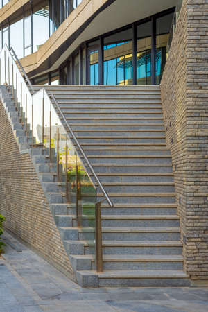 Stone staircase and railing leading to entrance of contemporary city office building with glass mirrored walls Stock Photo