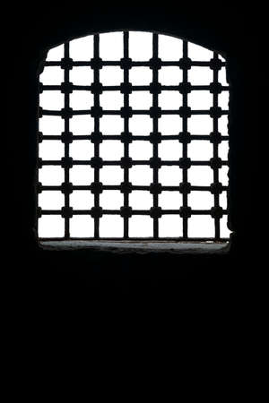 Cut out of arched window with metal grid in dark room of aged building against daylight, including clipping path