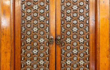 Closeup of wooden arabesque decorations tongue and groove assembled, inlaid with ivory and ebony, on door of Minbar of Imam Al Shafii public Mosque, Old Cairo, Egypt