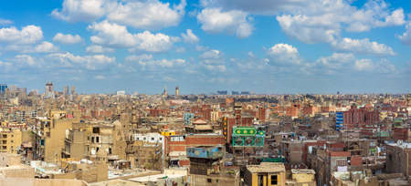 Panorama of shabby buildings with satellite dishes on rooftops against blue cloudy sky in ancient city of Cairo, Egypt Stock Photo