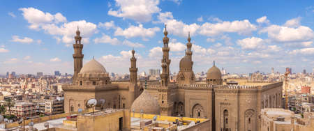 Aerial day shot of minarets and domes of Sultan Hasan mosque and Al Rifai Mosque mediating shabby buildings with satellite dishes in cloudy day, Old Cairo, Egypt