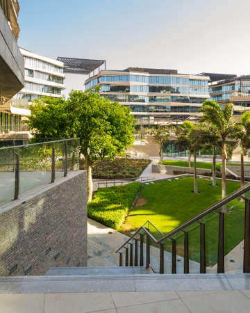Marble staircase and glass handrail leading to street in contemporary urban city district with well run glass buildings, verdant lawn, and palm trees on sunny day