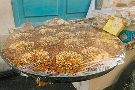 Sweets - traditional edible souvenirs from Tunisia. Arrangement of nuts on a large platter in the form of flowers. Medina, Sousse