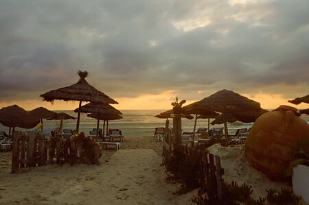 View of the beach at dawn with the sky covered by dark rain clouds. Nice beach with beach chairs and thatched umbrellas in Sousse, Tunisia 写真素材
