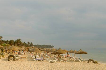 The comfortable sand beach with beach chairs and thatched umbrellas in Sousse. Cloudy sky in Tunisia