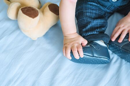 The hand of a 6-month-old child with curiosity touches his booties, next to which is a toy bear. First baby shoes, baby development concept Stockfoto