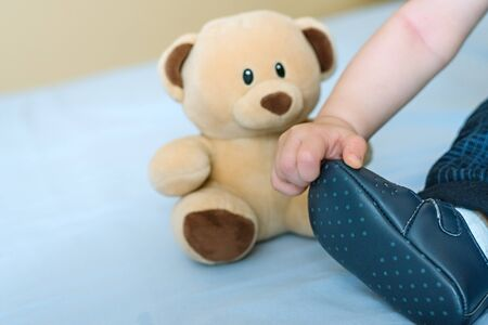 The hand of a 6-month-old child with curiosity touches his booties, next to which is a toy bear. First baby shoes, baby development concept Imagens