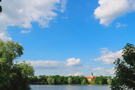 Panoramic view with a beautiful blue sky and clouds on the architectural complex Nesvizh Castle from the river. Postcard concept Postcard Concept- Welcome to Belarus.  Background image with copy space