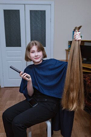 Young blonde girl cut very long hair at home