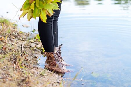 Feet in rubber boots with an animal print stand on the banks of the river. Autumn concept.