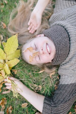 Portrait of a happy beautiful girl holding a bunch of fallen leaves. Positive woman is dreaming with closed eyes in the park while lying on the grass