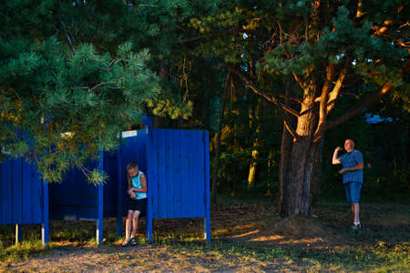 Separate blue beach changing- room on a background of pine trees. Europe. Belarus. Lake Dryvyaty