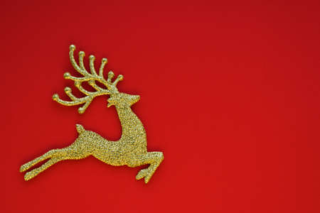 Christmas card concept. Christmas golden toy deer on a red background. Celebration concept