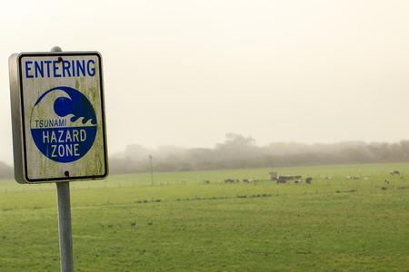 flood area warning sign: Tsunami hazard warning sign above low-lying fields