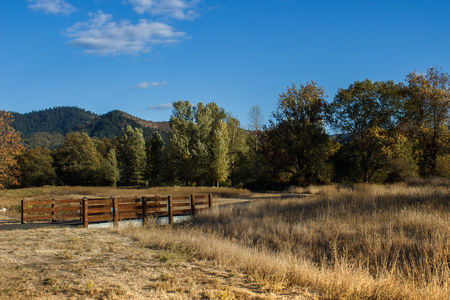 culvert: A wood and concrete bridge over a dry, grassy culvert Stock Photo