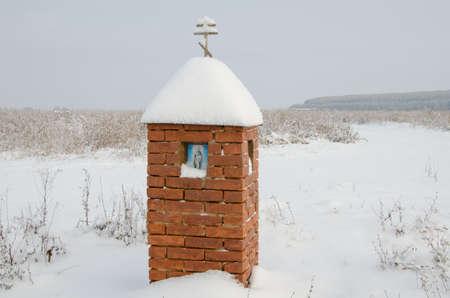 A small brick chapel in winter field.