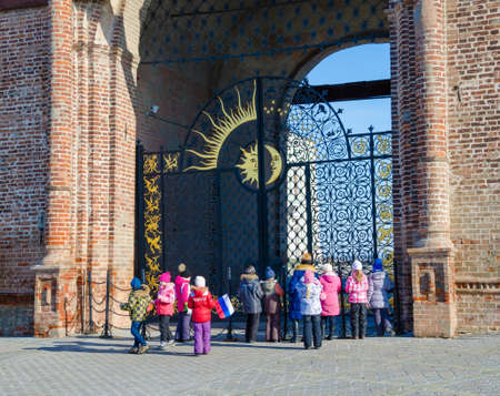 architectural heritage of the world: Kazan, Republic of Tatarstan, Russia - February 20, 2016: Historic and Architectural Complex of the Kazan Kremlin. UNESCO World Heritage Site. School excursion. The teacher-guide and group of schoolchildren near iron gate of the tower Syuyumbike.