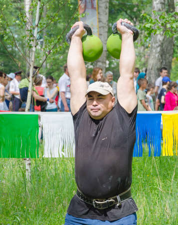 field work: Kazan, Republic of Tatarstan, Russia - May 28, 2016: Male athlete lifts weights. Sabantuy (translated from Tatar - feast of the plow) is a traditional celebration of the end of spring field work. Editorial